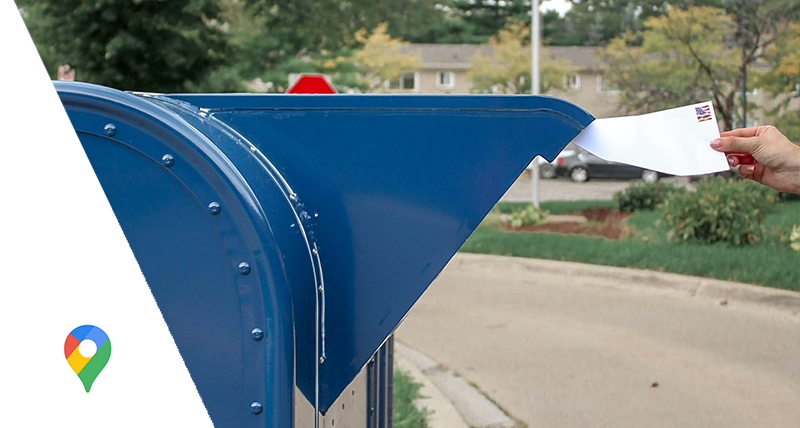 woman mailing a letter in US postal service drop box